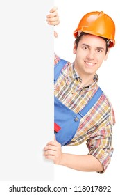 Young construction worker with helmet posing behind a blank panel isolated on white background