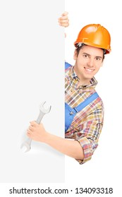 Young construction worker with helmet posing behind a panel and holding wrench isolated on white background