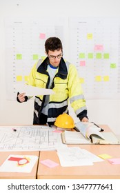 Young construction worker turning pages while holding blueprint in office