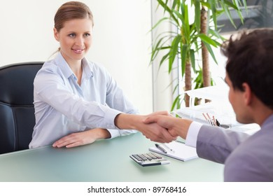 Young consultant shaking hands with her client