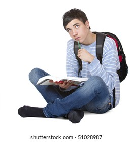 Young contemplative male student sitting on floor with book. Isolated on white.