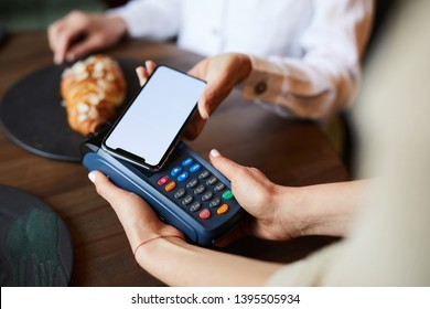 Young contemporary buyer using contactless payment system to pay for food and drink in cafe or restaurant