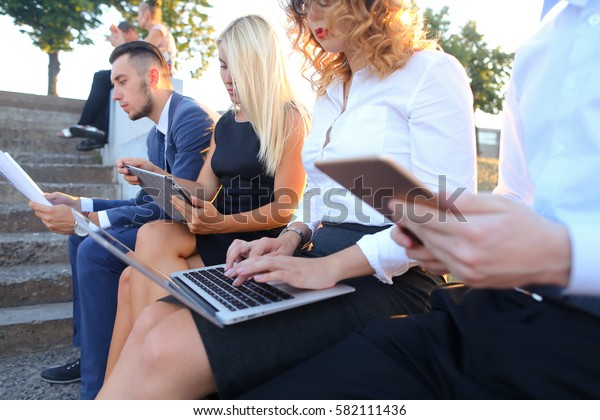 Young contemporary confident people, two boys and two girls, perspective entrepreneurs, students smiling, chatting with each other, using gadgets, laptops, tablet and smartphone for work with office