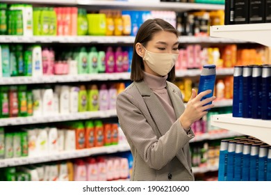 Young contemporary elegant female consumer standing by large shelf with shampoos and hair conditioners and choosing one in supermarket