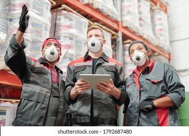 Young contemporary intercultural warehouse workers in respirators and workwear discussing new assortment of goods by huge rack
