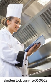 Young content chef using tablet standing in professional kitchen