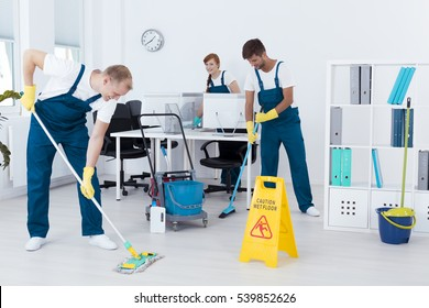 Young contract cleaners cleaning a modern office