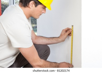Young contractor measuring the wall for repairing