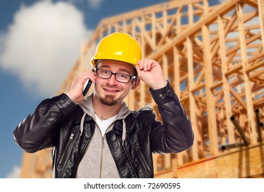 Young Contractor Wearing Hard Hat on Cell Phone In Front of Construction Site.