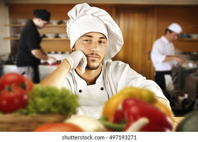 young cook chef in kitchen and blurred vegetables