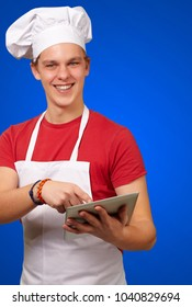 young cook holding a digital tablet isolate on blue background