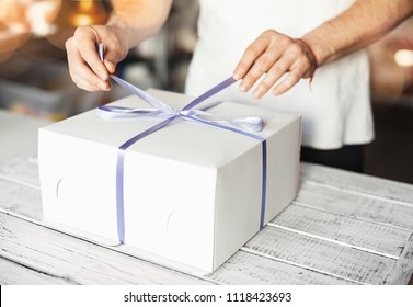 Young cook ties violet ribbon on white cake packaging