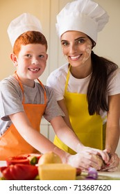 The young cook woman and her smilng son in cook form kneading the dough in the kitchen