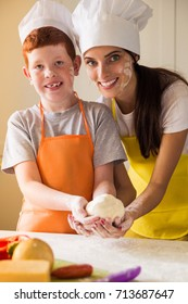 The young cook woman and her smilng son in cook form keeping the dough in hands in the kitchen