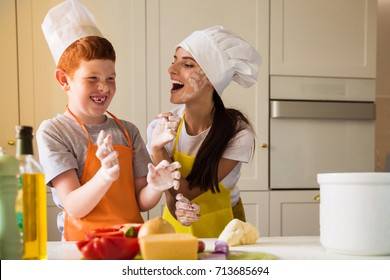 The young cook woman and her son in cook form kneading the dough and they dirtying of flour each other