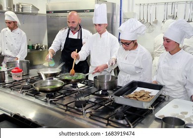 Young cooks prepare food in the kitchen. Puglia, Italy - 21/05/2016
