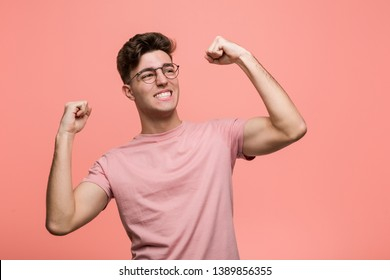 Young cool caucasian man raising fist after a victory, winner concept.