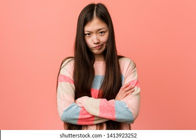 Young cool chinese woman frowning face in displeasure, keeps arms folded.
