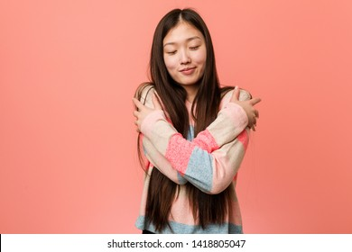 Young cool chinese woman hugs himself, smiling carefree and happy.