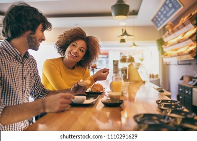 Young cool couple having a breakfast, they are drinking tea and coffee in a bakery, orange juice too, they feel comfortable and happy.
