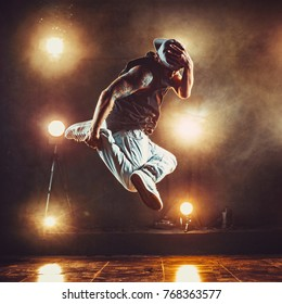 Young cool man break dancer jumping in club with lights and smoke. Tattoo on body.