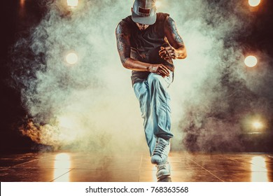Young cool man break dancing in club with lights and smoke. Tattoo on body.