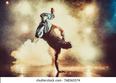 Young cool man break dancing in club with lights, smoke and water. Tattoo on body. - Shutterstock ID 768363574