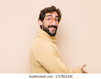 young cool man feeling happy and cheerful, smiling and welcoming you, inviting you in with a friendly gesture against flat wall