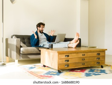 young cool man sitting on a sofa at living room watching tv