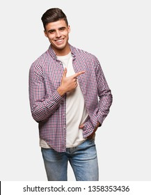 Young cool man smiling and pointing to the side