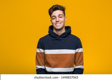 Young cool man wearing a hoodie happy, smiling and cheerful.