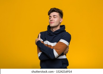 Young cool man wearing a hoodie hugs himself, smiling carefree and happy.