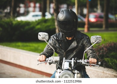 young and cool. motorcyclist on his bike and with helmet on his head riding motorcycle