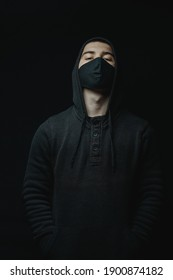 young cool rapper with black hoodie and face mask standing in front of black background