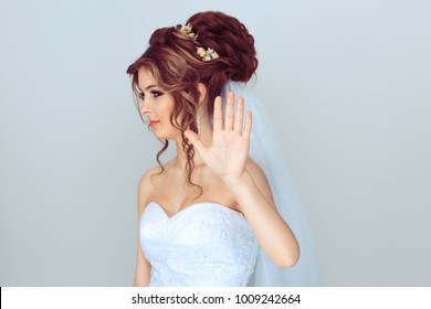 Young cool woman bride showing no stop sign with hand looking away to the side ignoring you isolated on light blue gray background