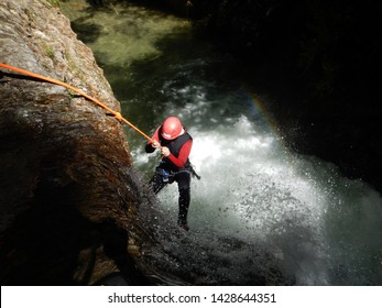 young corageous girl climbing down while canyoning - rappeling into the water in the canyon