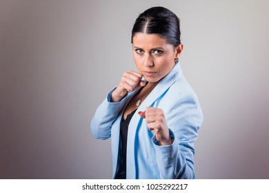 Young corporate lady strikes back, ready to fight and punch with her fists clenched
