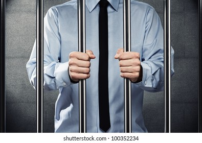 Young corrupted businessman in jail, behind the prison bars