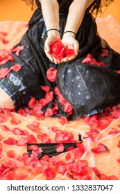 young cos player girl dress with black lolita costume holding a handful of petals, sit on  the yellow carpet which covered by red petals