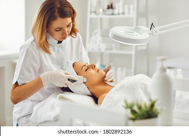 Young cosmetologist or dermatologist making ultrasound facial cleaning for woman in beauty salon
