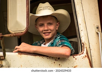 A young country boy with a cowboy hat on looking out the window of a old rusty vintage work truck- A happy, smiling teenager in the front seat of an old farm truck- A young man driving a old truck
