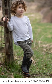 A young country boy with farm boots is standing next to a rustic fence in a meadow. The child is on a meadow outside. His tall rubber boots are for country life. The kid is next to a old wooden fence