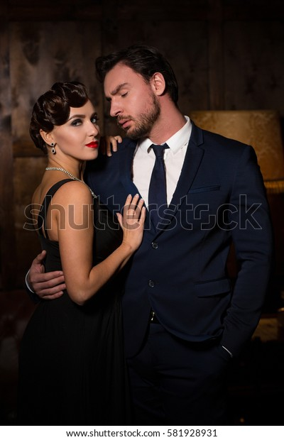 Young coupe posing for photographer. Beautiful woman with red lips dreaming about marry foreign millionaire. Rich businessman hugging vamp lady and trying to kiss her.