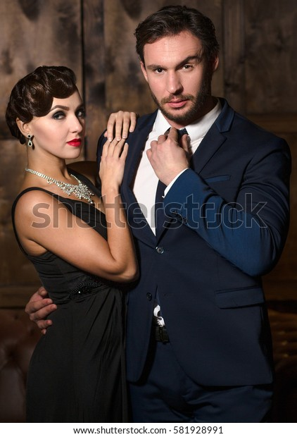 Young coupe posing for photographer. Rich businessman hugging vamp lady. Beautiful woman with red lips dreaming about marry foreign millionaire.