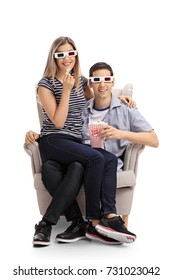 Young couple with 3D glasses and popcorn sitting in an armchair and looking at the camera isolated on white background
