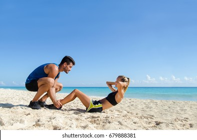 Young couple abs training at the beach