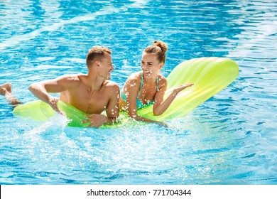 Young couple active leisure swimming pool concept