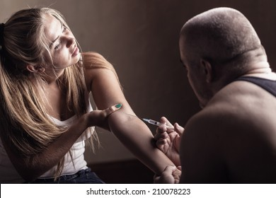 Young couple addicts. Man injects girlfriend drug into a vein