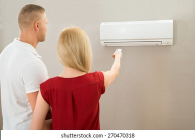 Young Couple Adjusting Temperature With Remote Control Of Air Conditioner