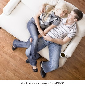 Young couple affectionately sit back on a cream colored love seat. Horizontal shot